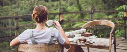 Una mujer disfrutando una taza de café producido de forma responsable en Costa Rica.